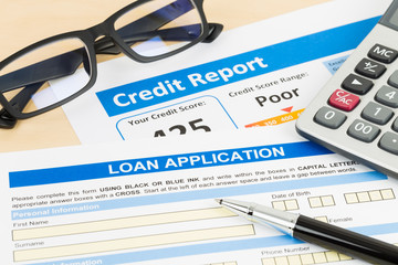 Loan application form poor credit score with calculator, glasses, and pen