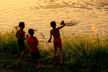 Local kids throuwing rocks in Nam Song River at sunset, Vang Vieng, Laos