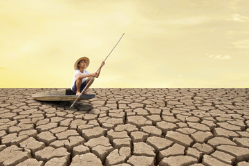 Climate change and Drought impact. Young man sitting on wooden boat at dry land.