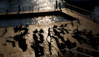 People enjoy a sunny evening at the harbour of Helsinki