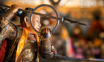 A statue of a holy warrior monk with spear in buddhist temple builing with copy space- thailand