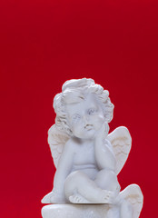 Figurine Of Baby Angel On Red Background