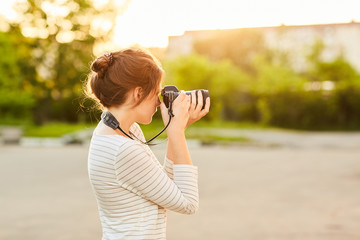 young girl taking pictures on camera in a summer Park at sunset