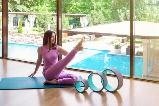 Young  sportswoman doing yoga or fitness exercises with wheel for yoga in the gym with  a panoramic window.  Outside the window you can see the park.