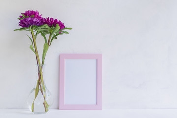 Mockup with a pink frame and pink flower in a vase
