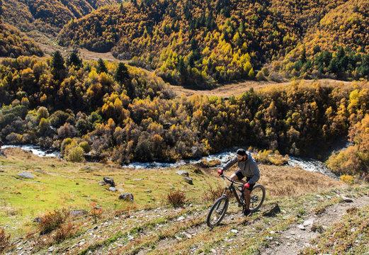 Mountain biker riding on bike in autumn mountains landscape