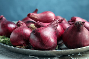 Plate with ripe red onions on table, closeup