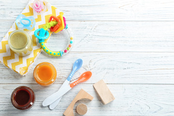 Flat lay composition with baby food and accessories on wooden background