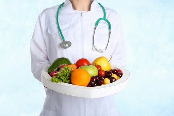 Female doctor with fresh products on light background. Cardiac diet