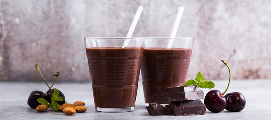 banner of Chocolate smoothies with cherries and almonds. on a table of gray stone. Vegan protein drink for athletes and gourmets