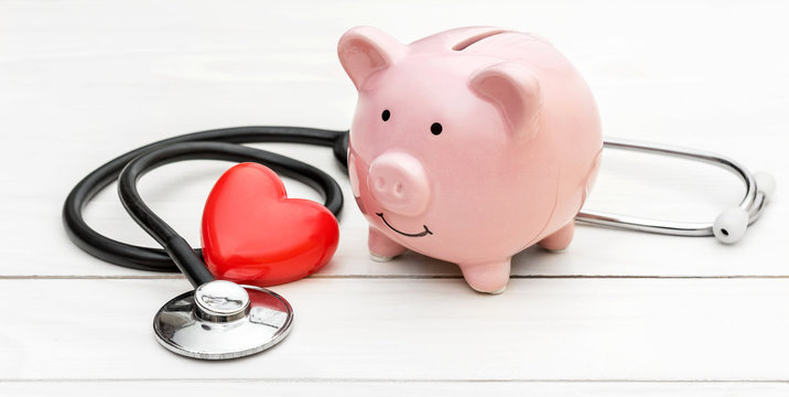 Piggy bank with stethoscope and red heart on white wooden table.