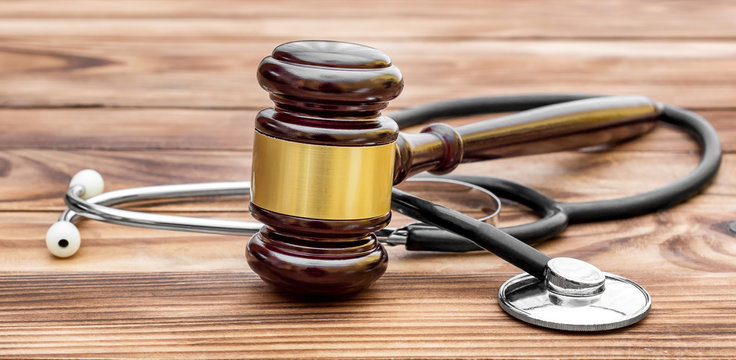 Gavel with stethoscope on wooden table. Medical law.