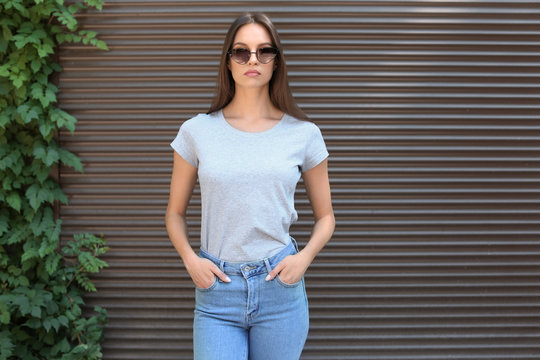 Young woman wearing gray t-shirt near wall on street. Urban style