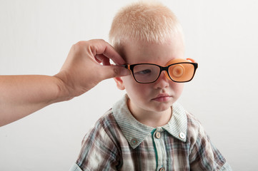 Careful Mother dresses baby glasses with Occluder. Ortopad Boys Eye Patces nozzle for glasses for treating strabismus (lazy eye) Female hands close-up.