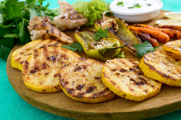 Grilled vegetables, fresh herbs, sauce on a wooden tray. Healthy food. A delicious appetizer.