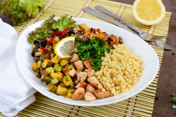 Delicious oriental salad tabbouleh. Couscous with fried vegetables and chicken on a white plate. Traditional Lebanese appetizer.