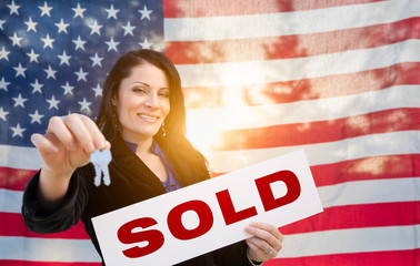 Hispanic Woman House Keys and Sold Sign In Front of American Flag