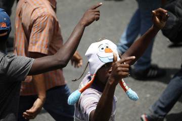 Demonstrators gesture as they march along a street during a protest in Port-au-Prince