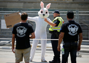 Protesters from the far-right group Storm Alliance look on as a counter-protester in a bunny costume gestures towards them on Parliament Hill in Ottawa