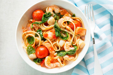 Seafood linguine with prawns, scallops and salmon, spinach and tomatoes