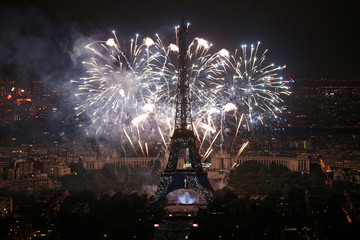 Fireworks explode around the Eiffel Tower, in a picture taken from the Montparnasse Tower Observation Deck, at the end of Bastille Day events in Paris