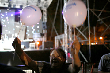 """An attendee holds balloons with the message """"Macedonia in NATO and the EU"""" during events organized by the government in 15 towns to celebrate an invitation for Macedonia to join NATO, in Skopje"""