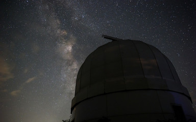 Dome of a small telescope in an observatory against the milky way