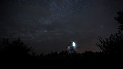 Open dome of a small telescope in an observatory in the background of the starry sky