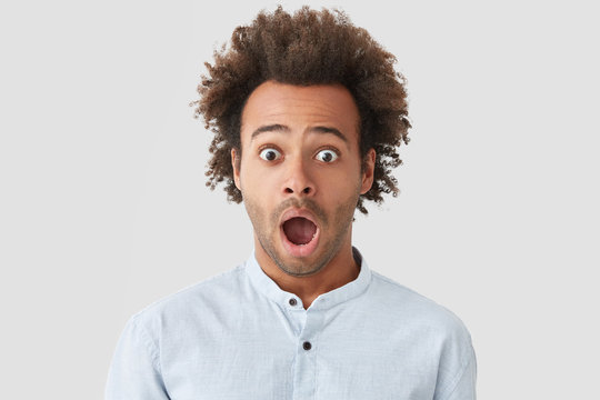Stunned handsome mixed race young male with bushy dark hair, keeps jaw dropped, opens eyes widely, can`t believe in bad fortune, expresses great surprisement, isolated over white background.