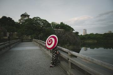 大阪城と和傘をさしている着物女性