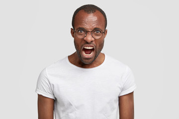 Negative human reaction concept. Angry furious young African American male exclaims, feels wretched while argues with someone, isolated over white background. Dark skinned guy screams nervously