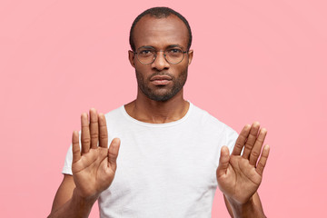 People and disagreement concept. Dark skinned serious male makes stop gesture, rejects something, stands indoor against pink background. African American man refuses drink alcohol, show no sign
