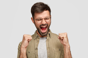 Crazy guy clenches fists and shouts angrily, expresses aggression and discontent, frowns face, feels wicked, dressed in fashionable shirt, stands against white background. Negative feeling concept