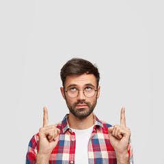 Good looking bearded young male points upwards with index fingers, focused above, has serious facial expression, advertises something, being confident in quality, isolated over white background