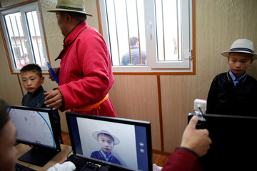 Child jockeys have their pictures taken and fingerprints registered before taking part in horse races at the Mongolian traditional Naadam festival, on the outskirts of Ulaanbaatar
