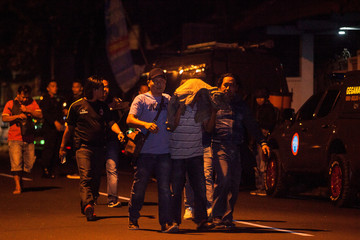 Police detain a suspect following the shooting of three suspected Islamic militants in Sleman