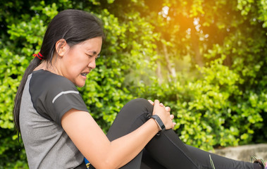 Woman suffering from pain in leg injury after sport exercise running jogging and workout outdoor