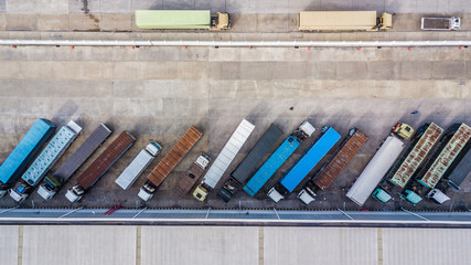 Aerial top view of truck and cargo trailer unloading in logostics center.