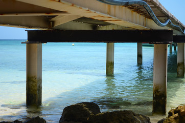 A wooden jetty stretching out into a tropical ocean. Sand and rocks can be seen through the clear water.