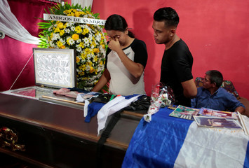 Mourners look into a coffin containing the body of Gerald Jose Vasquez,who died during clashes with riot police at the National Autonomous University of Nicaragua (UNAN), in Managua