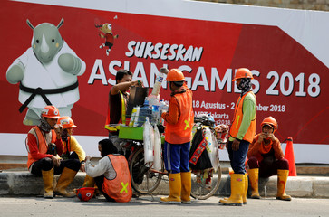 Construction workers take a break next to  a sign promoting the upcoming Asian Games in Jakarta