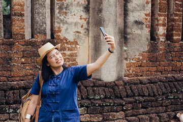Asian tourist woman selfie at ancient of pagoda temple thai architecture at Sukhothai Historical Park,Thailand. Female traveler in casual thai cloths style visiting city concept.