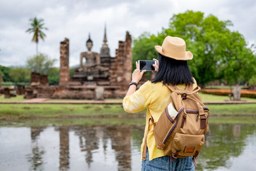Asian tourist woman use mobile take a photo of ancient of pagoda temple thai architecture at Sukhothai Historical Park,Thailand. Female traveler in casual thai cloths style visiting city concept.