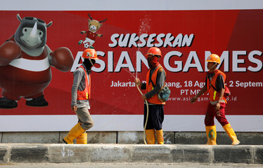 Construction workers are seen near a sign promoting the upcoming Asian Games in Jakarta