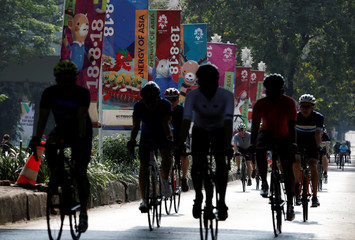 Cyclists ride past banners promoting the upcoming Asian Games to be held in Jakarta