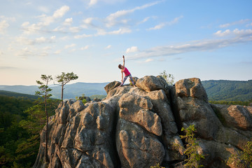 Attractive athletic girl doing complicated yoga exercises on top of huge pile of rocks on green mountains and clear blue sky background. Climbing, tourism, fitness and healthy lifestyle concept.