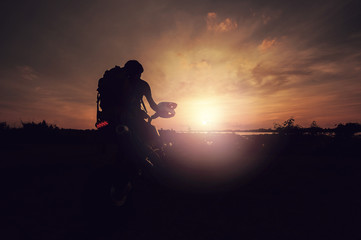 man and motorcycle in the sunset