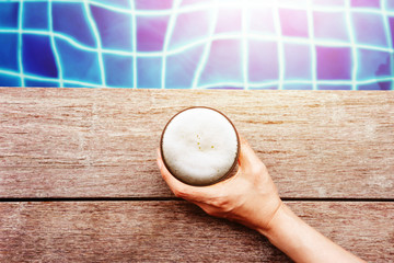 Drinking Beers in Summer r Fall Seson. Hand holding Glass of Beer Lay on the Swimming Poolside. Relaxation on Vacation or Holidays Concept. Top View