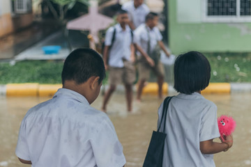 Boy and girl  wait to cross flooded street in heavy rainstorm be