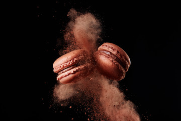 Macaron explosion. French chocolate macaron with cocoa powder against black background